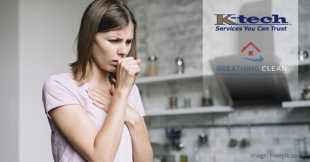 Woman standing in kitchen coughing into her hand