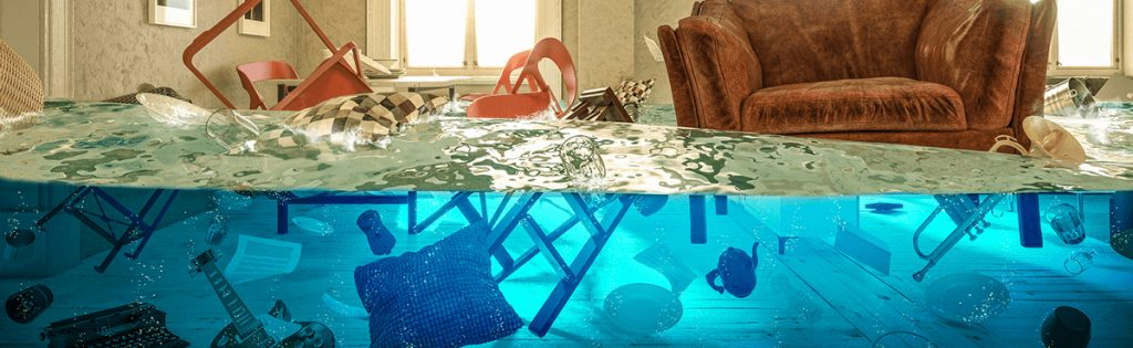 Flooded room in home with common household items floating in water.